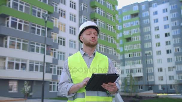 Kavkazská tvůrce s bílým chráněné přilbu a bezpečnostní vestu na staveništi pomocí tabletu pro výčepní něco. Venkovní