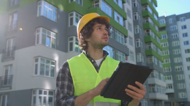 Young caucasian builder with yellow protected helmet and green safety vest using tablet for reporting his work. Outdoor.