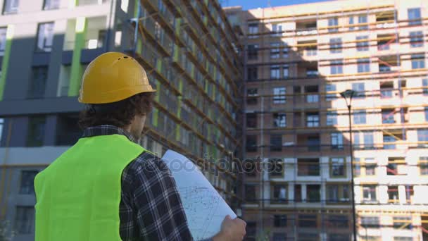 Back view of builder in protected helmet and vest looking drawing on unfinished construction background.