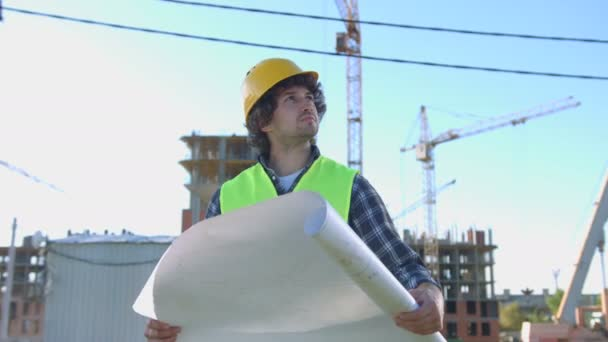 Young builder in protected yellow helmet and green vest looking and analysing drawing on unfinished construction background.