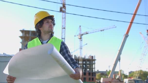Krásné mladé tvůrce v chráněných žlutou helmu a zelená vesta hledá stavební a analýzy výkresu na nedokončené konstrukce na pozadí.