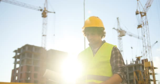 Concentrated young caucasian architect in yellow helmet standing on building background and looking drawing. Outdoor.