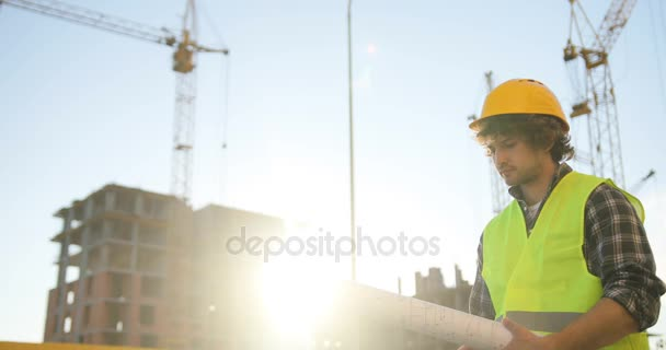 Side view of serious young caucasian architect in yellow helmet standing on building background and looking drawing. Outdoor.