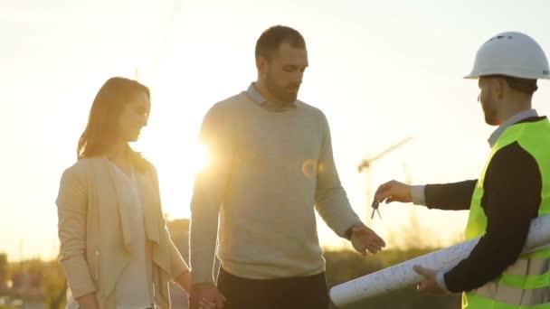 Boční pohled architekta v bílou helmu dávat keyses mladý pár klientů, potřásl rukou mužských klientů na slunce pozadí. Venkovní