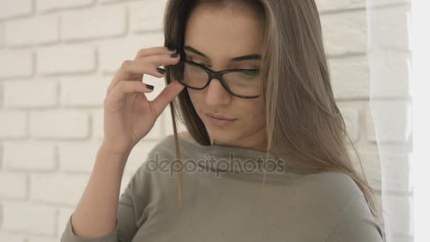 Portrét atraktivní mladá žena v neformálním oblečení s brýlemi vystupuje a usmívá se na kameru na bílém pozadí. Detailní záběr.