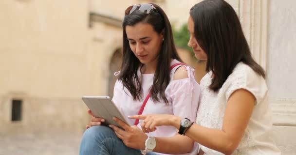 Dvě mladé roztomilé ženy drží tabletu a při pohledu na něj. Cítí se šťastný a nadšený. Venku.