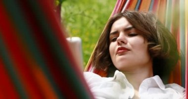 Young woman lying down on a hammock in summer forest using a digital tablet pc.