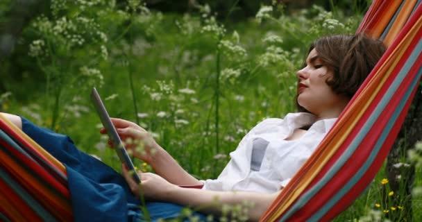 Mladá žena vleže v houpací síti v létě doménové struktury pomocí digitální tablet pc.