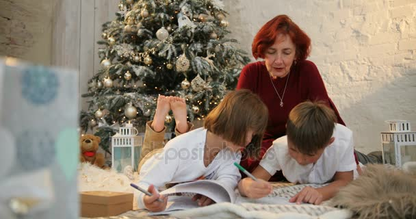 Grandmother and children near decorated christmas tree writing christmas letter to Santa Claus. The morning before Xmas. Family with kids celebrating. Christmas at home