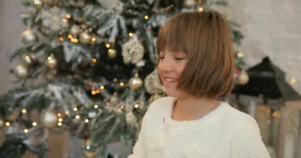 Malé radostné holčičky byly nadšeni s šumivé barevné konfety pádu všude kolem, vánoční stromeček pozadí. Vánoční svátky a nový rok.