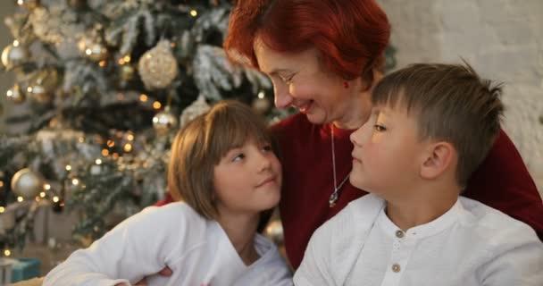 Babička, objal její vnoučata poblíž nazdobený vánoční stromeček. Ráno před vánočními. Rodina s dětmi doma slaví Vánoce