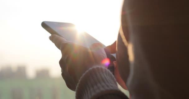 Ženská ruka hospodářství chytrý telefon. Dívka pomocí mobilního telefonu stoje u okna. Pohled zezadu zastřelil.