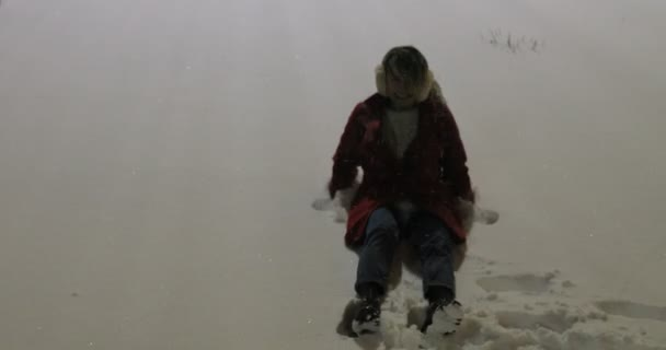 Mladá žena, takže sníh andělé v ve městě v noci