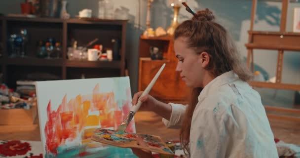 Blick zurück auf die junge, hübsche Malerin aus dem Kaukasus, die in der Werkstatt ein Bild malt und dann fröhlich in die Kamera blickt. Hinten.