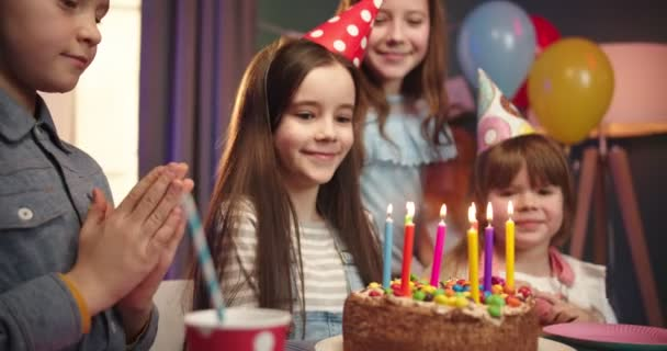 Close up of the birthday cake with candles on the table with happy birthday girl and her joyful friends on the background.