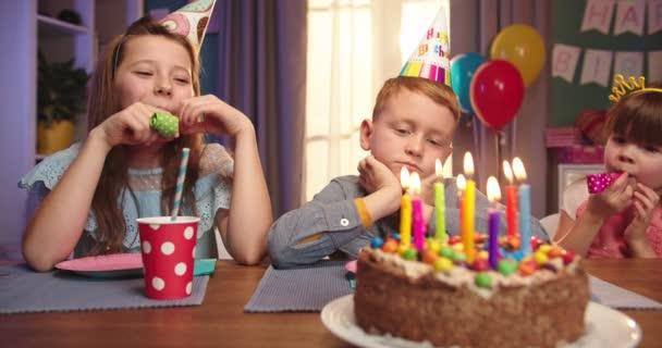 Porträt des kleinen netten, aber gelangweilten Kaukasischen Jungen im Konus, der mit anderen glücklichen Kindern am Geburtstagstisch mit einer Torte sitzt und unglücklich aussieht.