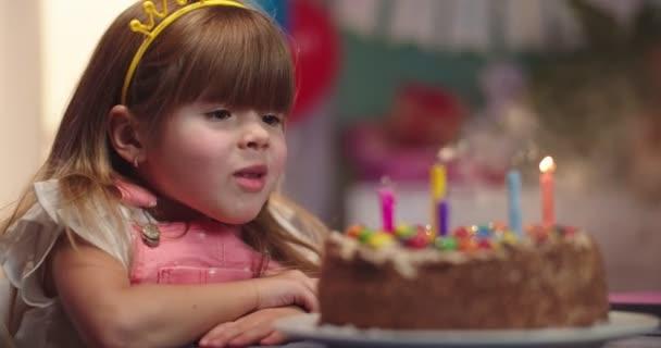 Porträt des niedlichen kleinen kaukasischen Mädchens, das am Tisch sitzt, Kerzen auf der Geburtstagstorte bläst und fröhlich lächelt. Nahaufnahme.