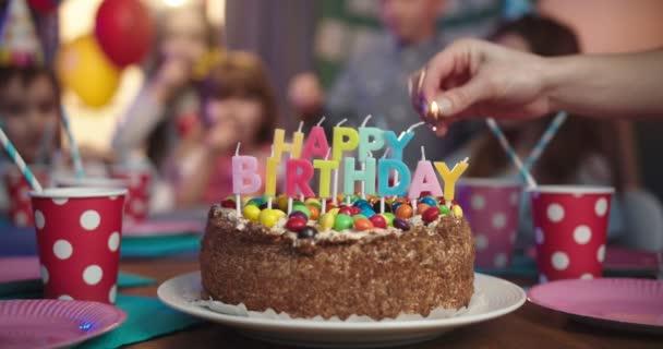 Ruka kavkazské ženy matka zapalování svíčky na dort s Happy Birthday slova, zatímco děti čekají na pozadí.