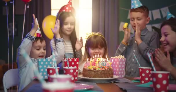 Narozeninová oslava malé kavkazské dívky: dívka foukání svíčky na dort a její malí přátelé tleskající a smějící se.