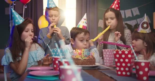 Kaukázusi kis aranyos szülinapos fiú elfújja a gyertyákat a tortán, miközben boldog barátai tapsolnak és mosolyognak. Születésnapi party gyerekeknek.