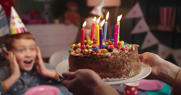 Detailní záběr na narozeninový dort s bonbóny a svíčkami v rukou ženy, zatímco ona přináší do jeho malého roztomilého syna k narozeninové párty.