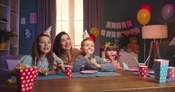 Vidám kaukázusi kisfiú a szülinapi kúpjában ül az asztalnál a barátaival és az anyjával, és vár, amíg valaki szülinapi tortát hoz az asztalra, aztán gyertyát fúj..
