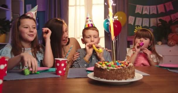 Veselý a šťastný běloch děti s narozeninovým chlapcem a matka sedí u stolu s dort a slaví narozeniny.