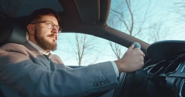 Oldalnézet a kaukázusi jóképű üzletember szemüveges vezetés egy szép autó és lisening a rádió.