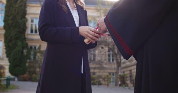 Mladá běloška krásná žena profesorka předává diplomy a certifikáty studentům na jejich maturitní den ze střední školy. Outdoor.