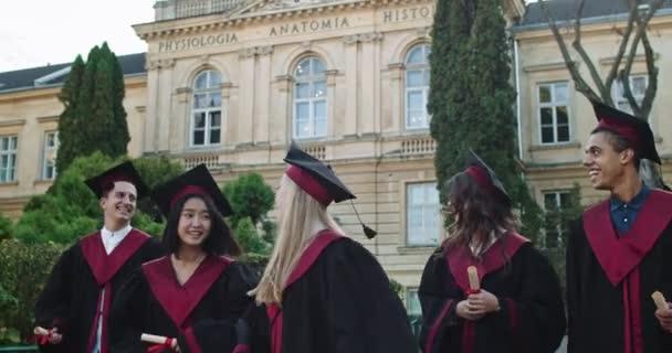 Fiatal vegyes versenyek vidám és boldog lányok és fiúk, érettségizett diákok vidáman sétálnak és szórakoznak, miután diplomát szereztek a diplomaosztón.