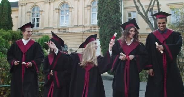 Vidám végzősök csoportja, vegyes fajú lányok és fiúk akadémiai sapkában és köntösben boldogok az egyetemi diplomák és bizonyítványok megszerzésének ceremóniája után. Kültéri.