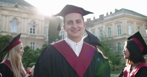 Portrait shot of the young and cheerful Caucasian guy, graduated student in the academic cap and gown smiling too the camera at the college building. Outdoors. Close up.