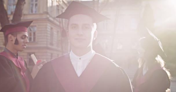Detailní záběr legrační mladý běloch šťastný muž absolvent akademické čepice a róby stojí před vysokou školou a usmívá se do kamery v jasném slunečním světle. Portrét.
