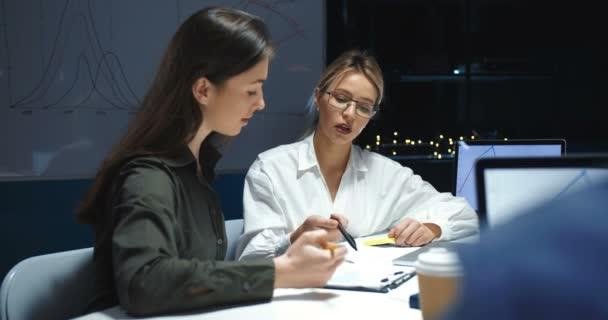 Kavkazská mladá zaměstnankyně z kanceláře, která si povídá a pracuje s dokumenty u notebooku pozdě večer. Ženy spolupracovnice brainstorming o nápady na projekt.