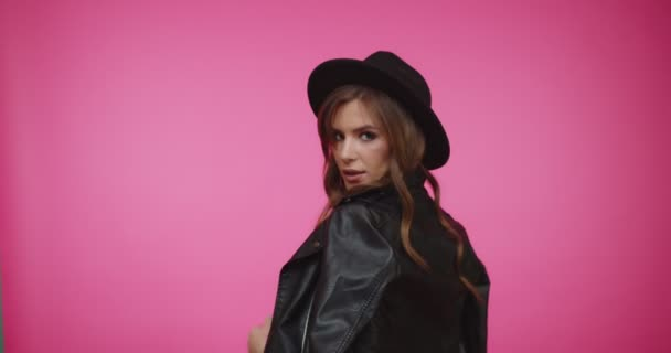 Fashion model turns around and looks into the camera. Girl with long brown hair. Attractive woman with flying curly hair. Beautiful brunette woman shaking hair and playing with her black hat.
