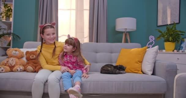 Portrét dvou veselých roztomilých malých bělošských sester sedících na gauči v útulném obývacím pokoji. Starší sestra objímající mladší. Pěkně šťastné děti v legračních uších, usmívající se doma na gauči.