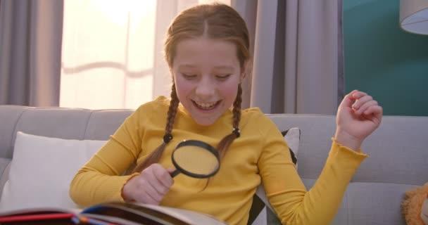 Kaukasisches niedliches Teenie-Kind liest Buch und sitzt auf dem Sofa im gemütlichen Wohnzimmer. Hübsches kleines Kind las Märchen. Mädchen erkunden Lehrbuch mit Lupe zu Hause. Kleines neugieriges Lesekonzept.