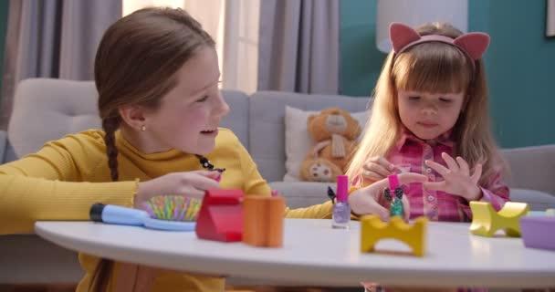 Kavkazské teen hezké dívky leštění a malování nehty, zatímco oni sedí doma sami. Malé děti si hrají v salónu krásy v útulném obýváku. Roztomilé děti dělají manikúru legrační.