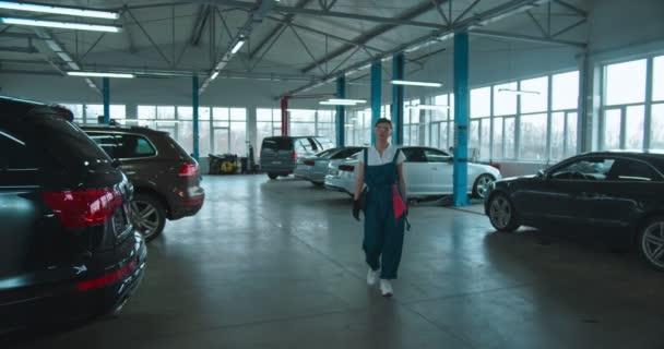 Kavkazská mladá krásná žena auta opravář v uniformě, brýle a s klíčem se blíží ke kameře ve velké garáži. Portrét krásné šťastné dívky mechanik vesele se usmívá.
