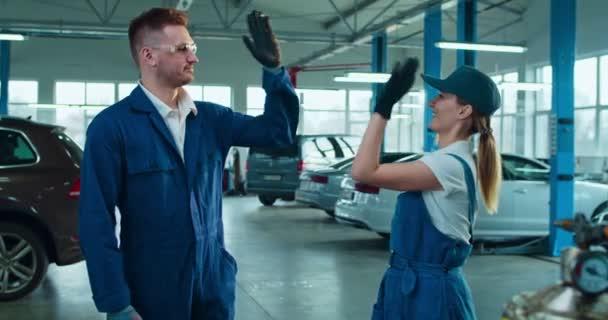 Pár samců a samic automechaniků v uniformách, kteří si navzájem dávají pět a radostně se smějí. Portrét krásné ženy a pohledný muž s úsměvem na kameru ve velké garáži.