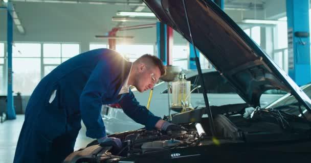 Kaukasischer junger Automechaniker steht am offenen Auto und repariert Motor in großer Garage. Ein Mann in Uniform und Brille arbeitet in einem Kfz-Reparatursalon. Verkehrskonzept.