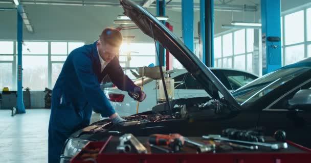 Muž Kavkazský mladý automechanik stojící u otevřeného auta a opravující motor ve velké garáži. Muž v uniformě a brýlích servisní vozidlo v autoopravně v interiéru. Koncept dopravních služeb