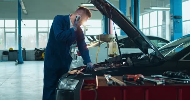 Muž běloch automechanik mluví na mobilním telefonu v otevřeném autě a opravuje motor v garáži. Muž v brýlích, pracující ve službě a mluvící na mobilu, jako by žádal o radu. Konverzace koncepce.