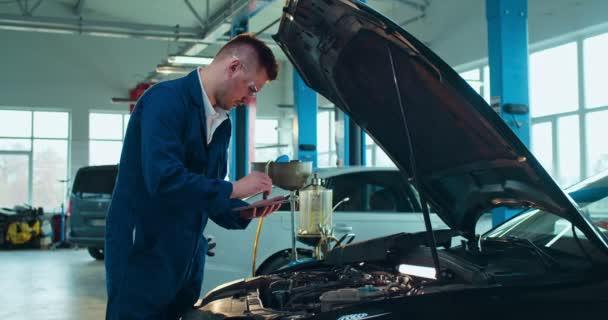 Muž Kavkazský mladý automechanik stojící u otevřeného vozu a opravující motor pomocí tabletu. Muž v uniformě a brýlích pracuje v automobilové službě s počítačem jako klepání a sledování tipy.