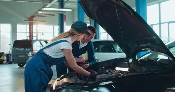 Kaukasischer Mann unterrichtet junge Frau in Overalls und Hut, um Auto in Auto-Service-Salon zu reparieren. Arbeiterin lernt und repariert Motor in großer Garage, während männlicher Kollege hilft und steuert.