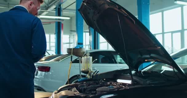 Bělošský mladík v uniformě a brýlích, který otevírá motor v autě a vyplňuje některé dokumenty perem ve složce. Mužský pracovník autoservisu psaní a zaznamenávání automobilových podmínek.