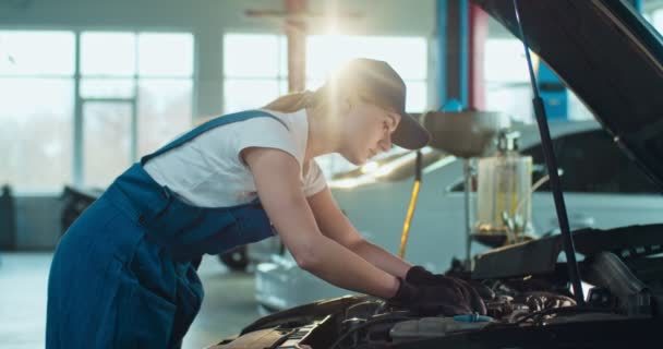 Mladá běloška žena auto inženýr stojí u otevřeného vozu a opravuje jeho motor ve velké dílně. Dělnice v uniformách a brýlích v garážích automobilových služeb. Koncept dopravních služeb.