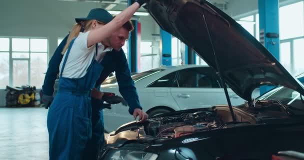 Kavkazská mladá žena auto servisní pracovník otvírá motor auta a ukazují přerušení problém mužské kolegy ve velké garáži. Mužský a ženský pár inženýrů pracujících společně nad automobilem.