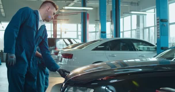 Běloch učí mladou dívku v uniformách opravovat auto v servisním salónu. Žena pracovnice učení zatímco muž kolega opravy motor ve velké garáži a říkat jí proces.