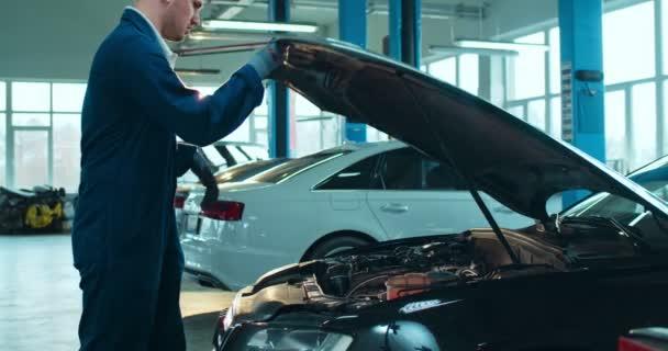 Kavkazský mladý muž z autoservisu přichází k autu, otevírá a hledá přestávku s baterkou v motoru v garáži. Muž inženýr opravy automobilů.
